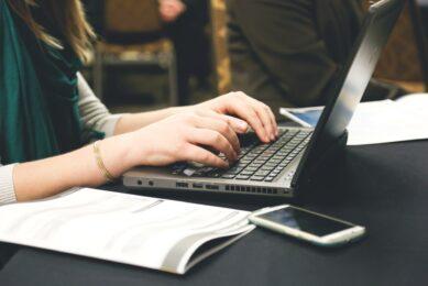 Kvinde skriver på computer med notesblog ved siden af
