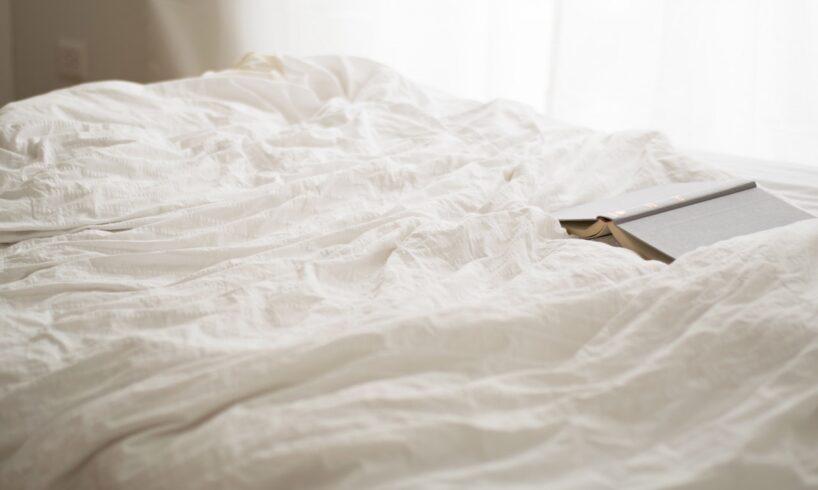 Hvidt betræk på seng med bog