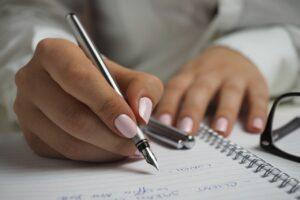 Person skriver i sin notesbog med kuglepen